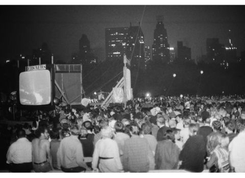 A large crowd watches the moon landing on a screen in Central Park.